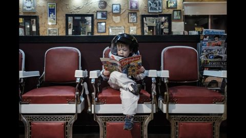"""Aaron Sheldon's son, Harrison, reads a magazine inside a Columbus, Ohio, barbershop. He is wearing an astronaut costume for Sheldon's project """"Small Steps Are Giant Leaps,"""" which illustrates how children -- like astronauts -- are constantly exploring the world around them."""