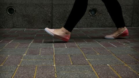 A woman walks over the sidewalk reinforced with glue to prevent the bricks from being dug up and used as projectiles.