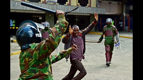 Kenyan riot police officers raise batons over a man during a demonstration of Kenya's opposition supporters in Nairobi, on May 16, 2016.  CARL DE SOUZA/AFP/Getty Images