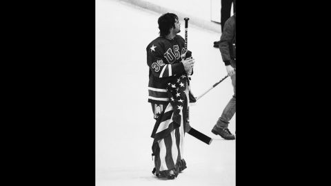 Jim Craig, goalie for the USA Olympic hockey team, holds the American flag on the ice rink after defeating Finland at the 1980 Olympics.