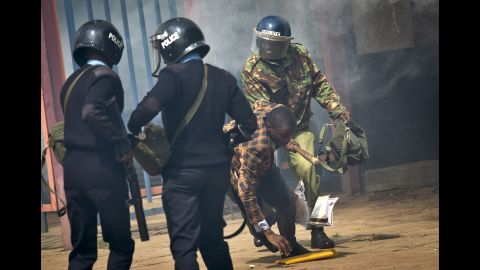 """An opposition supporter is beaten with a wooden club by riot police as he tries to flee. Kenyan police tear-gassed and beat opposition supporters <a href=""""http://www.cnn.com/2016/05/17/africa/kenya-police-violence/"""" target=""""_blank"""">during a protest</a> demanding the disbandment of the electoral authority over alleged bias and corruption."""