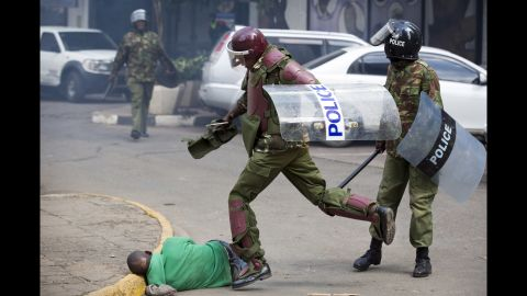 """A Kenyan riot policeman repeatedly kicks a protester as he lies in the street after tripping  while trying to flee from them on Monday, May 16. Ben Curtis, Associated Press' East Africa photographer and acting bureau chief in Nairobi said this man was """"chased across the street and fell down. As he lay motionless on the ground the riot policeman who had pursued him beat him with a stick, breaking it in half, and then continued to kick him half a dozen times, while two other police joined in. Eventually another officer walked up and directed the police to move away, leaving the man lying in the street. ... Later in the afternoon he was located in the Kibera slum of Nairobi -- injured but alive."""""""