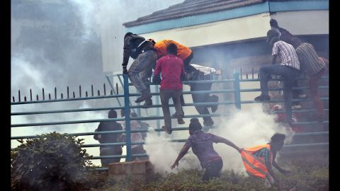 """Opposition supporters climb over a fence into the University of Nairobi campus as they flee from clouds of tear gas fired by riot police. """"The protests started a couple weeks ago, and have been taking place every Monday outside the offices of the electoral commission."""" Curtis said."""