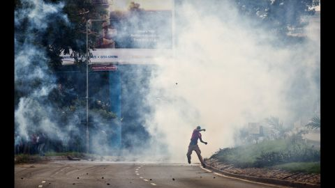 """An opposition supporter standing amid clouds of tear gas throws a rock toward riot police during a protest May 9. Curtis said, """"Many are hoping that some kind of political resolution of this issue can occur before the protests get further out of hand, but so far there are not many promising indications."""""""
