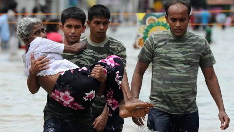 A member of a Sri Lankan Army rescue team carries an elderly woman to safety through floodwaters in Colombo on Wednesday, May 17, 2016. At least 19 were killed in the flooding or flood-triggered landslides. Army and navy teams have been deployed to rescue people marooned by the flooding.