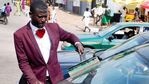 """Abdulahi Olatoyan wears sharp suits while working as a car window washer in Abeokuta, southwest Nigeria. """"I didn't want to be wandering around the streets doing nothing"""" he says."""