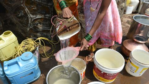 A villager filters her water through a sieve in Shahapur.