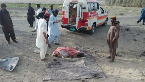 An unidentified body lies covered on the ground before being loaded into a waiting ambulance May 21.