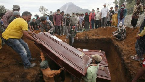 Coffins containing the bodies of the volcano eruption victims are lowered into a grave during a funeral Sunday, May 22.