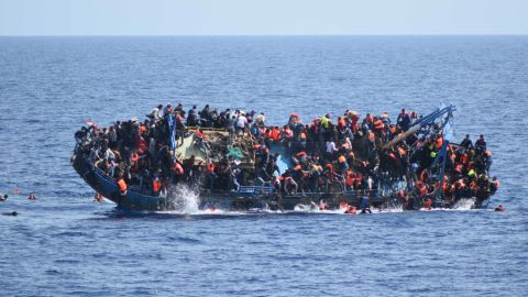 A ship crowded with people fleeing conflict in the Mideast flips onto its side Wednesday as an Italian navy ship approaches. Five people died and 500 were rescued.