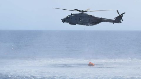 The helicopter hovers above the water during the rescue operations.