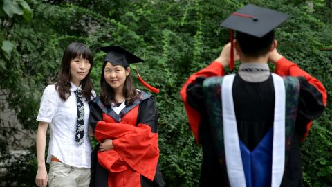 Students pose for photos after a graduation ceremony at a university in Beijing on July 11,2013. Despite a boom in student numbers in recent years, many graduates from second and third-tier institutions face considerable employment uncertainty in an economy largely fuelled by a blue-collar workforce.      AFP PHOTO / WANG ZHAO        (Photo credit should read WANG ZHAO/AFP/Getty Images)