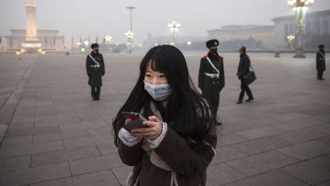 """BEIJING, CHINA - DECEMBER 09:  A Chinese woman looks at her phone as Chinese Paramilitary police wear masks to protect against pollution as they stand guard during smog in Tiananmen Square on December 9, 2015 in Beijing, China. The Beijing government issued a """"red alert"""" Sunday for the first time since new standards were introduced earlier this year as the city and many parts of northern China were shrouded in heavy pollution. Levels of PM 2.5, considered the most hazardous, crossed 400 units in Beijing, lower then last week, but still nearly 20 times the acceptable standard set by the World Health Organization. The governments of more than 190 countries are meeting in Paris to set targets on reducing carbon emissions in an attempt to forge a new global agreement on climate change.  (Photo by Kevin Frayer/Getty Images)"""