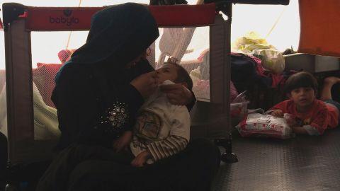 Johaina Daar talks tenderly to her son Alyaman while feeding him with a syringe.