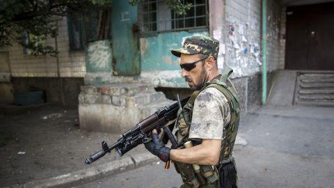 A pro-Russia rebel patrols a neighborhood near the central railway station in Donetsk, Ukraine in 2014.