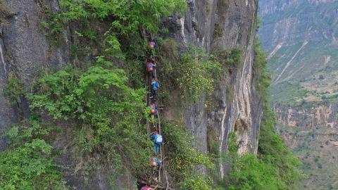 Children in Atule'er, a village in China's Sichuan province, climb a cliff to reach their school.