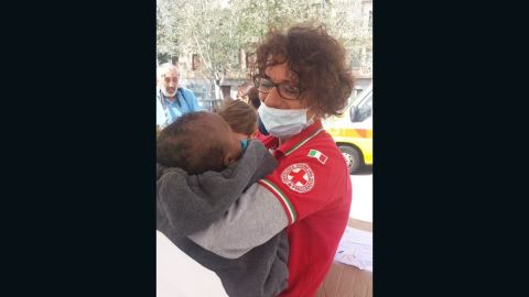 An Italian Red Cross worker holds a rescued migrant baby who arrived in Messina, Italy.