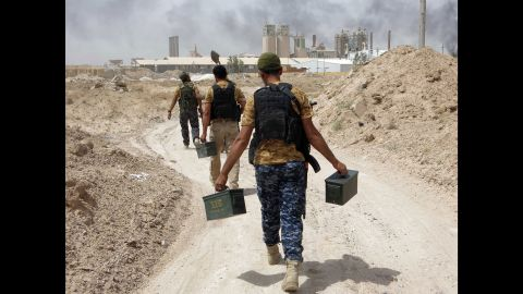 Pro-Iraqi government fighters carry ammunition in the village of Harariyat on Saturday, May 28.
