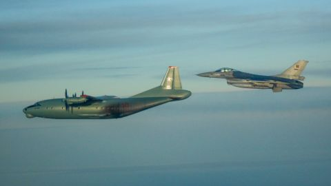 A Belgian F-16 watches a Russian An-12PPS.