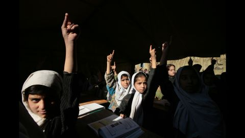 Afghan girls raise their hands during English class at the Bibi Mahroo high school in Kabul in November 2006. The overcrowded school was made up of UNICEF-supplied tents.