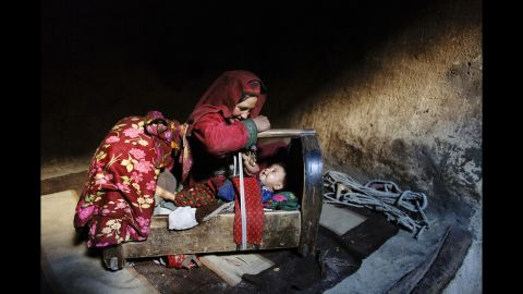 """A mother tends to her son inside their home in Afghanistan's <a href=""""http://cnnphotos.blogs.cnn.com/2014/06/22/on-top-of-the-world-untouched-by-war/"""" target=""""_blank"""">Wakhan Corridor</a> in October 2007."""