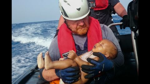 A member of the humanitarian organization Sea-Watch holds a migrant baby who drowned following the capsizing of a boat off Libya in May 2016.