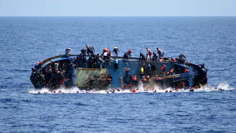 """A ship crowded with migrants <a href=""""http://www.cnn.com/2016/05/25/middleeast/migrant-ship-overturns/"""" target=""""_blank"""">flips onto its side</a> in May 2016 as an Italian navy ship approaches off the coach of Libya. Passengers had rushed to the port side, a shift in weight that proved too much. Five people died and more than 500 were rescued."""