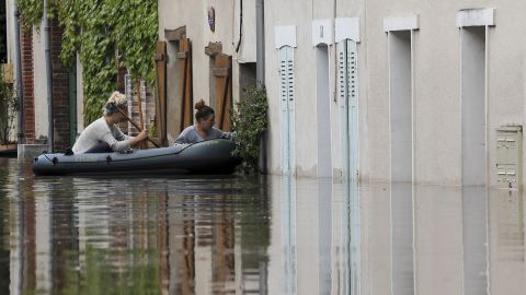 Two women try to enter their flooded home from an inflatable raft in Montargis on June 1.
