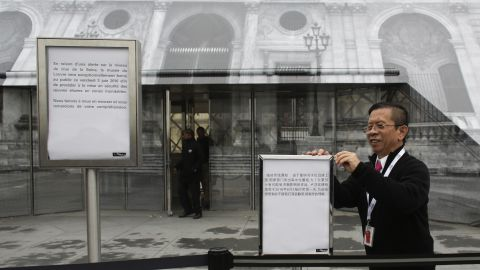 Staff of the Louvre post signs on June 3, informing visitors about the closing of the famous museum due to flooding in the city.