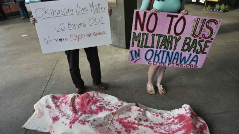 Activists, including some who are covered in mock shrounds, take part in a demonstration to protest against the US military presence in Okinawa, Japan, outside of Union Station in Washington, DC on May 26, 2016.