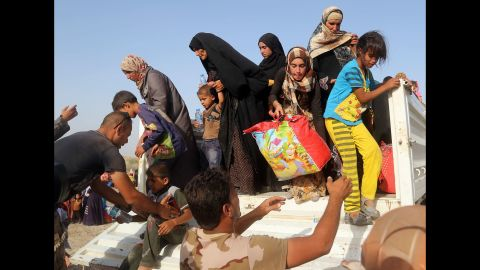 Iraqi soldiers help civilians from a vehicle outside a camp near Falluja on Friday, June 3.
