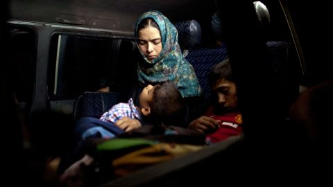 A boy sleeps in his mother's arms after fleeing from their home in Falluja on Monday, June 6.