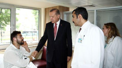 Turkish President Recep Tayyip Erdogan visits a man injured in the blast.