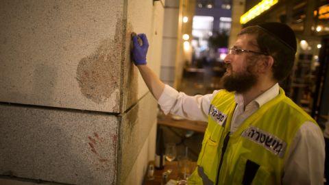 An investigator works the scene of the attack at Tel Aviv's Sarona Market.