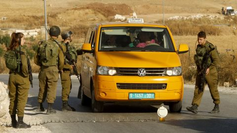 Israeli soldiers man a temporary checkpoint at the entrance of the Palestinian village of Yatta in the occupied West Bank on June 9,2016 after the army entered the village in search for clues leading to an attack the previous night in the Israeli city of Tel Aviv in which four people were killed and 16 others wounded.  The two Palestinians assailants who carried out the attack came from Yatta, according to Israeli authorities. Israel said it had suspended entry permits for 83,000 Palestinians during the holy Muslim month of Ramadan following the shooting attack.   / AFP / HAZEM BADER        (Photo credit should read HAZEM BADER/AFP/Getty Images)
