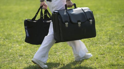 """A White House military aide and member of the US Navy carries a briefcase known as the """"football,"""" containing emergency nuclear weapon codes, as US President Barack Obama departs on Marine One from the South Lawn of the White House in 2012."""