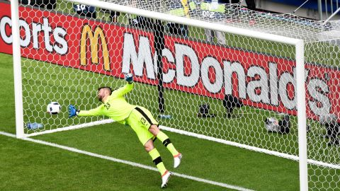 Matus Kozacik of Slovakia dives in vain as Gareth Bale scores a free kick goal.