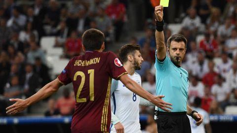Italian referee Nicola Rizzoli presents Russia defender Georgi Shchenniko, left, with a yellow card.