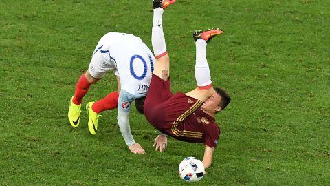 England forward Wayne Rooney, left, collides with Russia midfielder Aleksandr Golovin.
