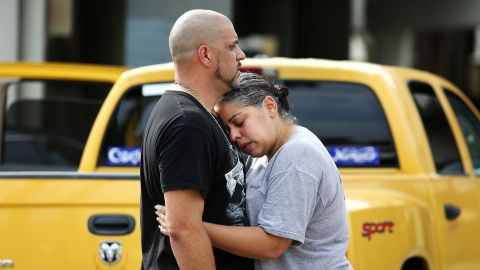Ray Rivera, a DJ at the nightclub, is consoled by a friend outside of the Orlando Police Department.