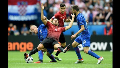 Croatia's Domagoj Vida, left, competes for the ball with Turkey's Cenk Tosun.