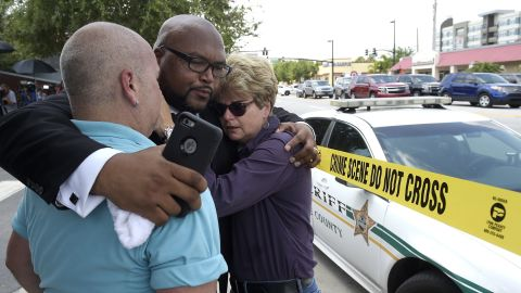 Pastor Kelvin Cobaris embraces Orlando City Commissioner Patty Sheehan, right, and Terry DeCarlo, executive director of the LGBT Center of Central Florida, on June 12.