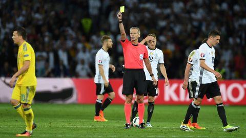 Referee Martin Atkinson gives a yellow card to Ukraine midfielder Yevhen Konoplyanka.