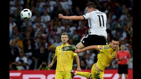 Draxler heads the ball over Artem Fedetskiy.