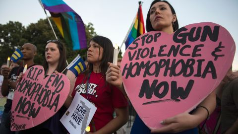 Mourners hold up signs during a vigil in Washington, DC on June 12, 2016, in reaction to the mass shooting at a gay nightclub in Orlando, Florida.  Fifty people died when a gunman allegedly inspired by the Islamic State group opened fire inside a gay nightclub in Florida, in the worst terror attack on US soil since September 11, 2001.