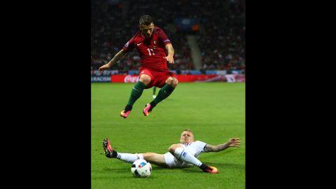 Vieirinha jumps over a tackle from Iceland's Ari Skulason.