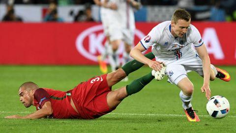 Portuguese defender Pepe collides with Jon Dadi Bodvarsson.