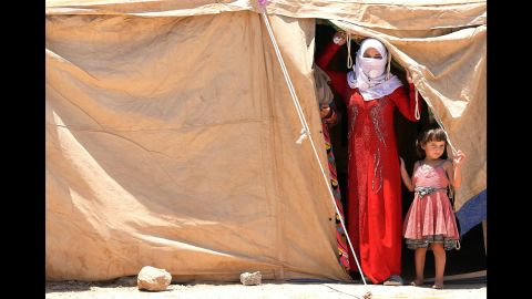 Iraqis who have been displaced from their homes peer out of a tent at a camp outside Falluja on Tuesday, June 14.