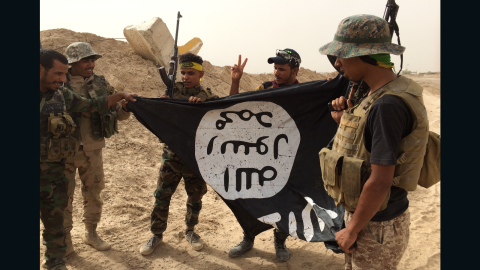 Group of Iraqi soldiers proudly pick up ISIS flag left behind