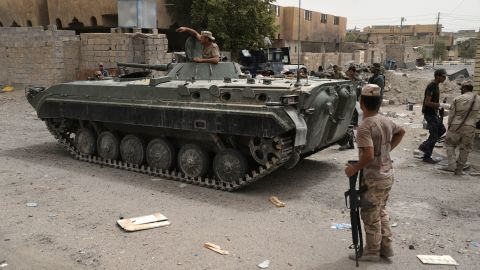 """Iraqi government forces patrol the centre of the city of Fallujah on June 18, 2016 as they hunt down holdout jihadists after retaking the Islamic State (IS) group's last remaining major hub in Iraq. While not fully under government control yet, Fallujah is the latest in a string of battlefield losses for IS, which has seen its two-year-old """"caliphate"""" shrink significantly in recent months.   / AFP / STRINGER        (Photo credit should read STRINGER/AFP/Getty Images)"""